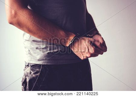 Handcuffed soldier in military army clothes. Prisoner of war or arrested terrorist, close up of hands in handcuffs, selective focus.
