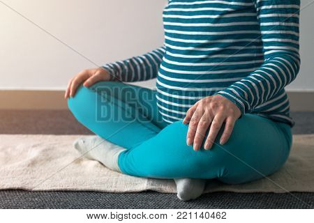 Pregnant woman practicing yoga exercise at home. Pregnancy yoga and indoors fitness concept. Ungraded low contrast footage with natural window light.