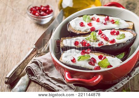 Grilled eggplants with garlic yogurt sauce and pomegranate in red form for baking over wooden background