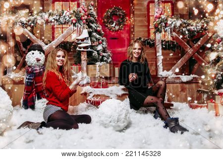 Happy girls in beautiful winter clothes make snowballs near the house, decorated for Christmas. Time of miracles. Merry Christmas and a Happy New Year.