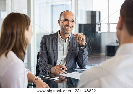 Mature financial agent in meeting sitting with young couple. Happy consultant talking with couple about their savings plan. Insurance advisor in a meeting with man and woman.