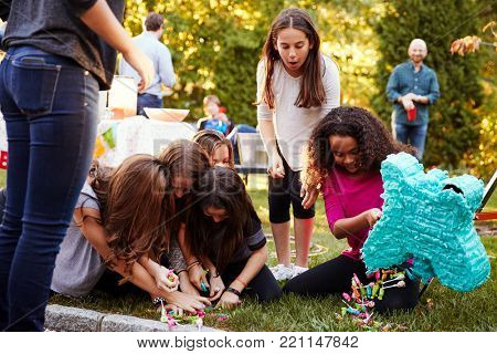 Young girls collecting sweets from a broken piâ??ata