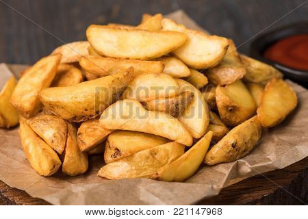 Roasted potato wedges on cutting board