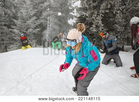 Group sportspeople on mountain making snowballs and having fun
