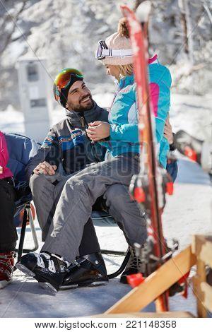 Woman on skiing in mountain  sitting in man's lap