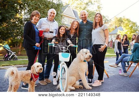 Neighbours with pet dogs smiling to camera at a block party