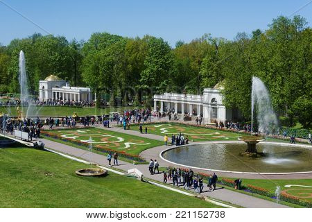 PETERHOF, ST. PETERSBURG, RUSSIA - JUNE 4, 2017: Tourists walking around the French fountain and the Grand Cascade. The cascade was built in 1715-1724