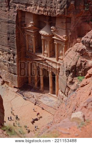PETRA, JORDAN - MARCH 16, 2014: Bedouins with their camels and tourists in front of Al Khazneh, the Treasury of Petra. Since 1985, Petra is listed as UNESCO World Heritage site