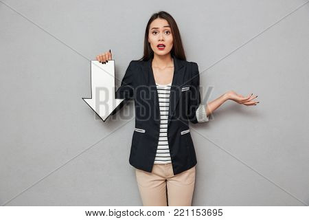 Surprised asian business woman shrugs her shoulders and pointing with paper arrow down while looking at the camera over gray background