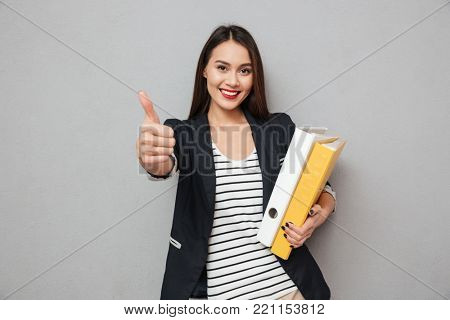 Happy asian business woman holding folders and showing thumb up while looking at the camera over gray background