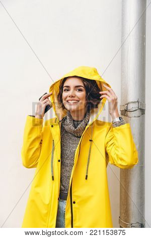 Smiling adult girl in yellow coat putting hood on head posing on camera with candid smile, being happy