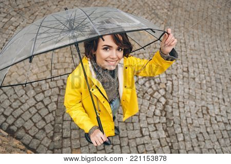 Shot from above of wonderful woman in yellow raincoat being happy, while walking under big transparent umbrella
