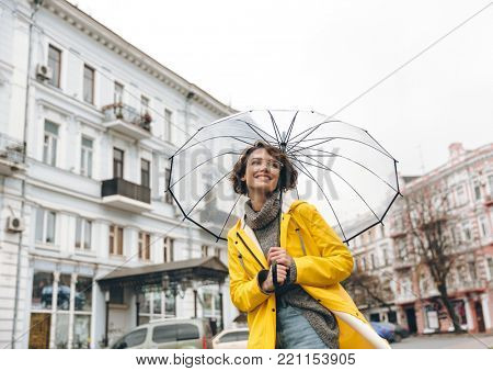 Optimistic woman in yellow raincoat and glasses having fun while walking through city under big transparent umbrella, during cold rainy day