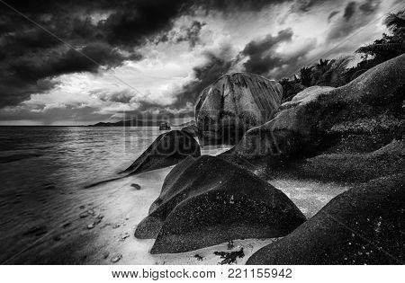Beautifully shaped granite boulder is washed by sea at Anse Source d'Argent beach, La Digue island, Seychelles. Black and white