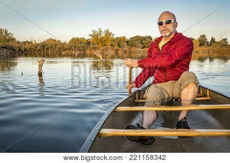 senior paddler enjoying paddling a canoe on a calm lake, Riverbend Ponds Natural Area, Fort Collins, Colorado