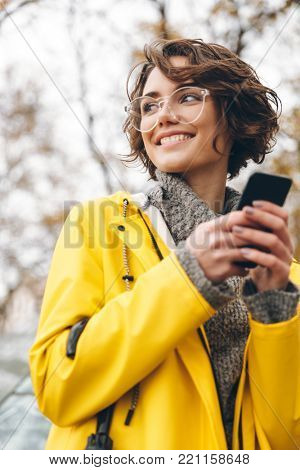 Smiling nice woman in yellow raincoat typing text message or scrolling feed in social network, using her smartphone while being outdoor