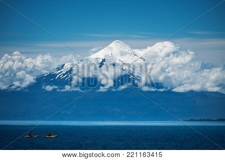 Two explorers paddling kayaks on the lake with volcano on the background. Volcano of Osorno, Chile