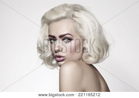 Vintage style portrait of young beautiful woman with platinum blonde hair and fresh make-up  poster