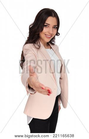 smiling young business woman welcomes with a handshake on white background