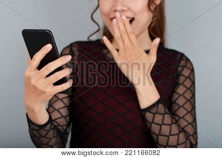 Cropped image of young woman reading shocking news on her phone