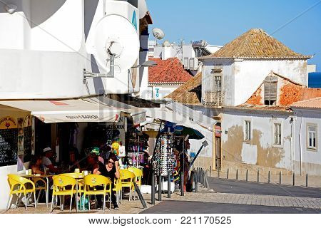 ALBUFEIRA, PORTUGAL - JUNE 6, 2017 - Tourists relaxing at a bar with tourists shops to the rear in the old town, Albufeira, Algarve, Portugal, Europe, June 6, 2017.