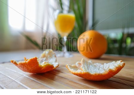 Tangerine peel with glass of orange juce on the background of a home plants.