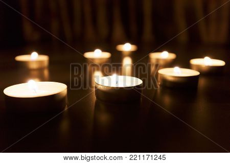 The candles glow. Dark background and Christmas candles are burning. The warm light of the candles is a symbol of the Christmas holiday