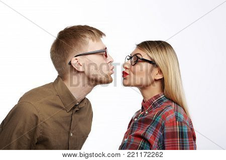 Fashionable young male with stubble and beautiful stylish female pouting their lips and closing eyes, about to kiss. Sideways portrait of cute sweet hipster couple in love preparing for kissing