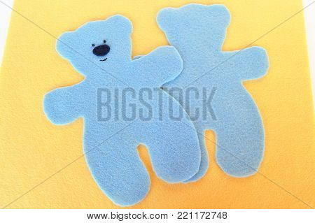 Handmade felt blue bear set on wooden yellow felt. Set for making bears from felt. Sewing concept. Sew toy