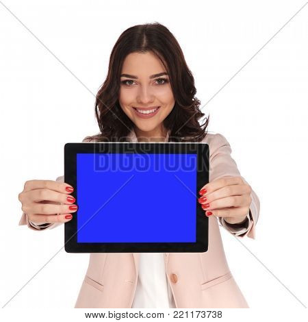 smiling young business woman showing blank screen of a tablet on white background
