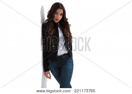 serious fashion woman leaning on white wall and poses for the camera in studio