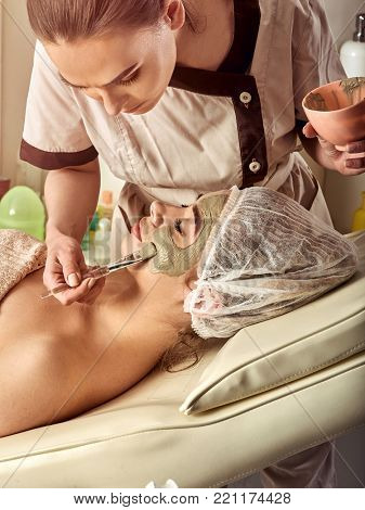 Mud facial mask of woman in spa salon. Massage with clay full face. Girl on with therapy room. Female lying wooden spa bed. Beautician with bowl therapeutic procedure isolated background. Removing