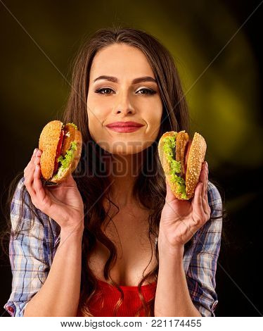 Woman eating hamburger.Day of discounts. One hamburger as sale gift. Student consume fast food. Girl bite of very big burger . Girl trying to eat a lot of junk on black background.