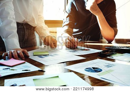 business meeting concept, calculate financial & budget & stock market data document with calculator in working on wood desk in office.