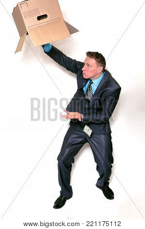 Businessman is holding a cardboard box and shaking out from it a money savings isolated on white background. Pay the debts. Savings. Bankrupt.
