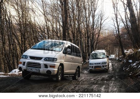 Stepantsminda, Gergeti, Georgia - October 22, 2016: Off road trip by Mitsubishi Delica Space Gear on dirty road in winter mountains.