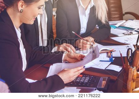 Business people office life of team working with papers sitting table with schemas and diagrams. Chief approve result of work of collective.