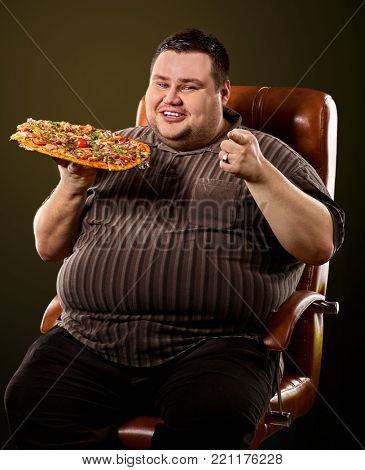 Fat man eating fast food and offers great pizza to customers . Male treats chic junk meal to friends. Breakfast for overweight person. leads to obesity. Advertising healthy food.