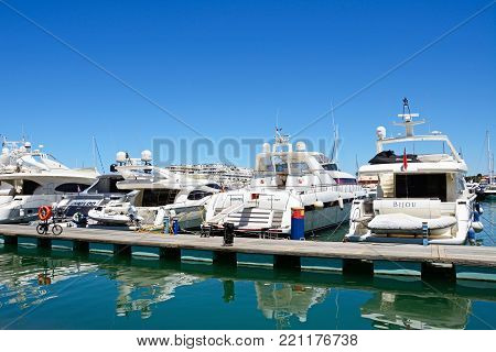 VILAMOURA, PORTUGAL - JUNE 6, 2017 - Luxury boats moored against a pontoon in the marina, Vilamoura, Algarve, Portugal, Europe, June 6, 2017.