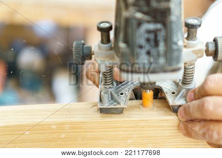 Carpenter working over door edge creating hinges holes with specific machine