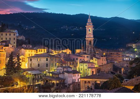 Cityscape of Dolcedo at dusk - small town located in Ligurian Alps, Italy. The main landmark is the bell tower of Church of Saint Thomas (Chiesa di San Tommaso)