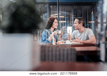 Warm atmosphere. Positive delighted woman sitting opposite her friend and holding cup of coffee in both hands while being in all ears