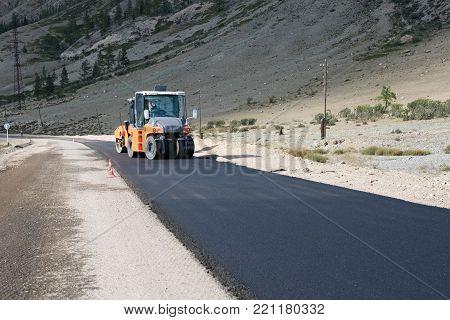 Asphalt paver of orange color rolls black asphalt for a road in the mountains in summer