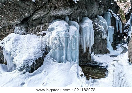 Hiking trail through a narrow gorge covered with snow and ice, mountain range Little Fatra, Slovakia, Europe.