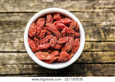 Dried goji berries in bowl on wooden background.