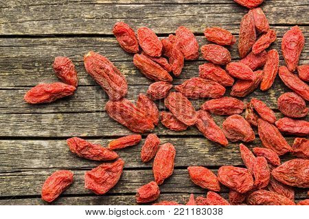 Dried goji berries on old wooden table.