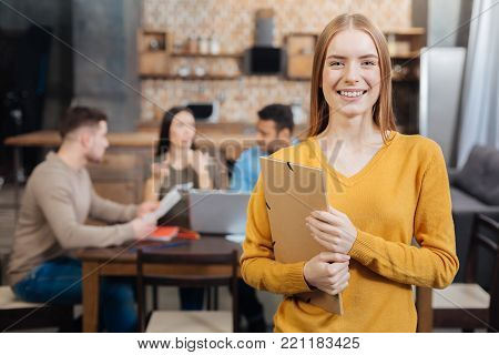 Pretty. Positive emotional young woman smiling and holding a big folder while her smart enthusiastic colleagues sitting behind her back and working