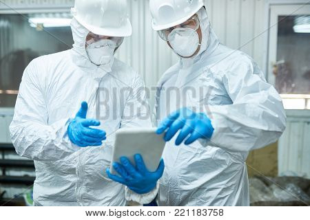 Portrait of two workers  wearing biohazard suits working at waste processing plant using digital tablet, copy space