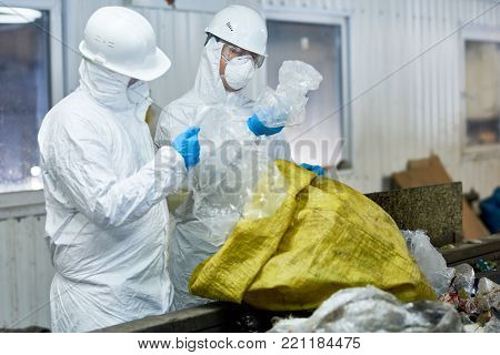 Portrait of two workers  wearing biohazard suits working at waste processing plant sorting recyclable plastic on conveyor belt