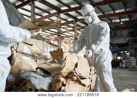 Portrait of  factory worker wearing biohazard suit sorting recyclable cardboard on waste processing plant, copy space